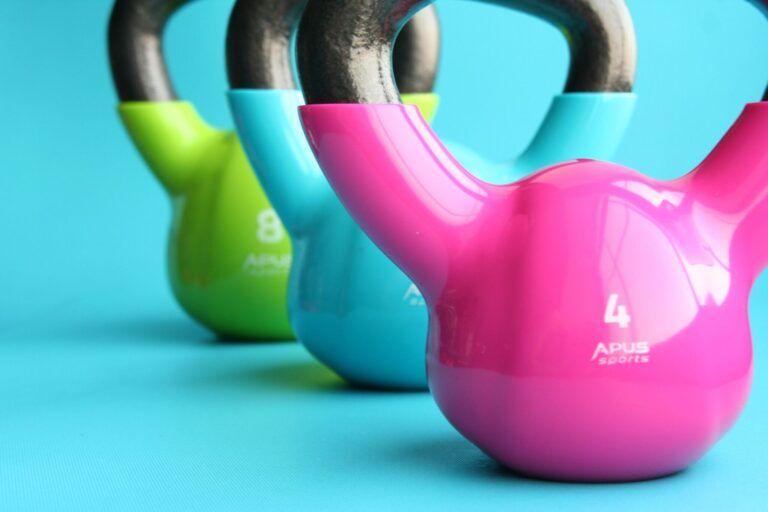 Vægte i henholdsvis pink, blå og grøn farve på blå baggrund