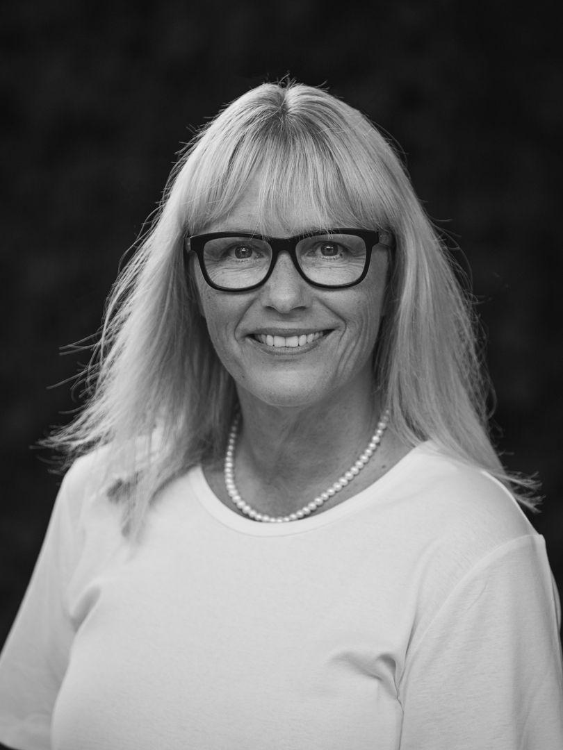 Middelaldrende kvinde med lyst gråt hår med briller og perle halskæde iført hvid t-shirt i sort og hvid